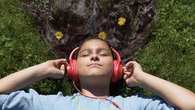 Ένα κορίτσι με τα μακρυμάλλη ψέματα στη χλόη στο πάρκο και ακούει τη μουσική στα ακουστικά κίνηση αργή HD φιλμ μικρού μήκους