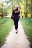 Ένα κορίτσι με τα ξανθά μαλλιά περπατά στο πάρκο μια ηλιόλουστη ημέρα άνοιξη στοκ φωτογραφία