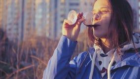 Ένα κορίτσι με τα ποτήρια του κρασιού στα χέρια της, που στηρίζονται στη φύση και στο ηλιοβασίλεμα 4K 3840x2160 φιλμ μικρού μήκους