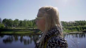 Ένα κορίτσι με την άσπρα τρίχα και τα γυαλιά είναι στο υψηλό ανάχωμα του ποταμού Οι βλαστοί καμερών στο σχεδιάγραμμα πρόσωπο κινη φιλμ μικρού μήκους
