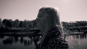 Ένα κορίτσι με την άσπρα τρίχα και τα γυαλιά είναι στο υψηλό ανάχωμα του ποταμού Οι βλαστοί καμερών στο σχεδιάγραμμα πρόσωπο κινη απόθεμα βίντεο
