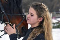 Ένα κορίτσι με τη μακριά ξανθή τρίχα επικοινωνεί με το αγαπημένο άλογό της Το κορίτσι τελείωσε ένα άλογο Μια νεφελώδης χειμερινή  Στοκ Εικόνες
