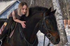 Ένα κορίτσι με τη μακριά ξανθή τρίχα επικοινωνεί με το αγαπημένο άλογό της Το κορίτσι αγαπά τα ζώα άνοιξη ημέρας ηλιόλουστη Κινημ Στοκ Φωτογραφίες
