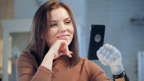 Ένα κορίτσι με τις βιονικές συζητήσεις προσθέσεων σε ένα τηλέφωνο, κλε απόθεμα βίντεο