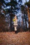 Ένα κορίτσι με τις κίτρινες τουλίπες την πρώιμη άνοιξη σε ένα κρύο βράδυ κοντά στον ποταμό στοκ εικόνες με δικαίωμα ελεύθερης χρήσης