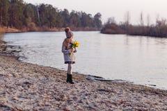 Ένα κορίτσι με τις κίτρινες τουλίπες την πρώιμη άνοιξη σε ένα κρύο βράδυ κοντά στον ποταμό στοκ φωτογραφίες με δικαίωμα ελεύθερης χρήσης