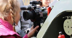 Ένα κορίτσι με τις πλεξίδες εξετάζει τη θέα πυροβόλων όπλων στην έκθεση του στρατιωτικού εξοπλισμού απόθεμα βίντεο