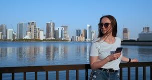 Ένα κορίτσι με τους μακρυμάλλεις πίνακες ένα μήνυμα στο smartphone στην αποβάθρα του Ντουμπάι απόθεμα βίντεο