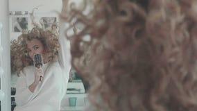 Ένα κορίτσι με τους σγουρούς ανόητους τρίχας μπροστά από έναν καθρέφτη και τραγουδά σε μια χτένα απόθεμα βίντεο