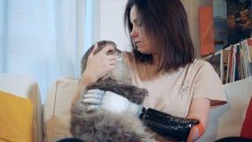 Ένα κορίτσι με το βιονικό χέρι κτυπά ελαφρά μια γάτα, κλείνει επάνω φιλμ μικρού μήκους