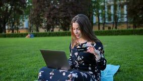 Ένα κορίτσι με ένα lap-top και μια πιστωτική κάρτα υπαίθρια απόθεμα βίντεο