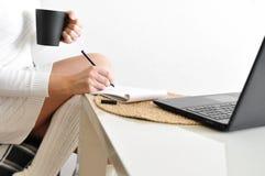 Ένα κορίτσι νοικοκυρών σε ένα άνετο άσπρο πουλόβερ και τις κάλτσες σε μια καρέκλα με ένα κάλυμμα εργάζεται με ένα lap-top στην κο στοκ φωτογραφία με δικαίωμα ελεύθερης χρήσης