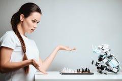 Ένα κορίτσι παίζει με ένα ρομπότ στο σκάκι Το ρομπότ κάθεται απέναντι από την στον πίνακα Στοκ εικόνα με δικαίωμα ελεύθερης χρήσης