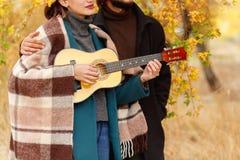 Ένα κορίτσι παίζει σε ένα ukulele κοντά σε έναν τύπο κινηματογραφήσεων σε πρώτο πλάνο σε ένα φθινοπωρινό θολωμένο υπόβαθρο Στοκ Εικόνες