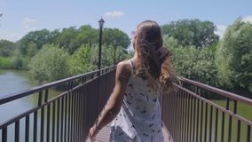 Ένα κορίτσι περπατά στο πάρκο, με ακολουθεί απόθεμα βίντεο