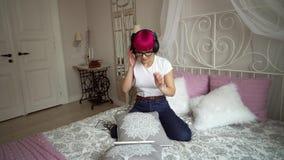 Ένα κορίτσι που ακούει τη μουσική στα ακουστικά στο κρεβάτι φιλμ μικρού μήκους