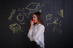 Ένα κορίτσι που δαγκώνει ένα κόκκινο μήλο, που στέκεται κοντά σε έναν πίνακα με τις εικόνες των σημαδιών των ιδεών, της επιστήμης στοκ φωτογραφία με δικαίωμα ελεύθερης χρήσης