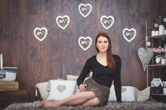 Ένα κορίτσι που εγκαθιστά με τις καρδιές στο backgound Στοκ Φωτογραφίες