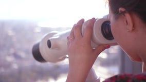 Ένα κορίτσι που κοιτάζει μέσω ενός μεγάλου ζευγαριού των διοπτρών που εξετάζει μια πόλη κίνηση αργή HD, 1920x1080 απόθεμα βίντεο