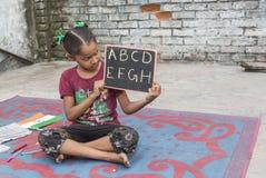 Ένα κορίτσι που μελετά τη στοιχειώδη εκπαίδευση στο ανοικτό σχολείο Στοκ Φωτογραφίες