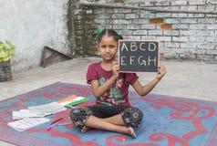 Ένα κορίτσι που μελετά τη στοιχειώδη εκπαίδευση στο ανοικτό σχολείο Στοκ εικόνες με δικαίωμα ελεύθερης χρήσης