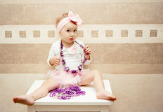 Ένα κορίτσι που ντύνεται επάνω όπως μια κούκλα κάθεται σε ένα στήθος των συρταριών Στοκ φωτογραφία με δικαίωμα ελεύθερης χρήσης