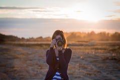 Ένα κορίτσι που παίρνει μια φωτογραφία με ένα DSLR με το ηλιοβασίλεμα στο υπόβαθρο στοκ εικόνα με δικαίωμα ελεύθερης χρήσης