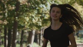 Ένα κορίτσι που τρέχει στα τρεξίματα Forest Park γύρω από μια κάμψη με τη κάμερα που ακολουθεί την από το μπροστινό 120fps απόθεμα βίντεο
