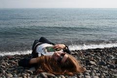 Ένα κορίτσι που φορά τα γυαλιά ηλίου βρίσκεται σε μια παραλία χαλικιών στοκ εικόνα με δικαίωμα ελεύθερης χρήσης
