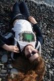 Ένα κορίτσι που φορά τα γυαλιά ηλίου βρίσκεται σε μια παραλία χαλικιών στοκ εικόνες