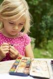 Ένα κορίτσι που χρωματίζει με τα υδατοχρώματα (watercolors), που χρωματίζουν ένα πιάτο εγγράφου Στοκ Φωτογραφίες