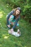 Ένα κορίτσι σε έναν κήπο που κτυπά ελαφρά να βρεθεί στο κουνέλι χλόης με ένα λουρί Στοκ φωτογραφία με δικαίωμα ελεύθερης χρήσης