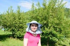Ένα κορίτσι σε έναν κήπο φρούτων που φορά ένα καπέλο μελισσοκόμων ` s στοκ φωτογραφία με δικαίωμα ελεύθερης χρήσης