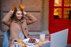 Ένα κορίτσι σε έναν καφέ που μιλά σε κάποιο σε ένα lap-top και που κάνει τα αυτιά των πεσμένων φύλλων υπαίθρια Στοκ φωτογραφίες με δικαίωμα ελεύθερης χρήσης