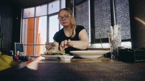 Ένα κορίτσι σε έναν όμορφο καφέ που τρώει μια σαλάτα των λαχανικών και επικοινωνεί με τη συνεδρίαση συντρόφων του απέναντι από Άπ φιλμ μικρού μήκους