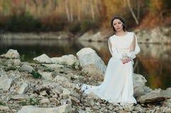 Ένα κορίτσι σε ένα άσπρο φόρεμα στην ακτή μιας λίμνης στοκ εικόνα