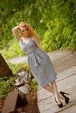 Ένα κορίτσι σε ένα απλό φόρεμα που στέκεται στην πορεία στο πάρκο στοκ φωτογραφία