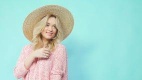 Ένα κορίτσι σε ένα καπέλο αχύρου και ένα καλοκαίρι ντύνουν τις στροφές και παρουσιάζουν ένα φόρεμα απόθεμα βίντεο