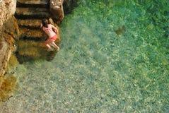 Ένα κορίτσι σε ένα κόκκινο κοστούμι λουσίματος που ξεπερνά τη θάλασσα και που αναρριχείται σε έναν βράχο Στοκ φωτογραφίες με δικαίωμα ελεύθερης χρήσης