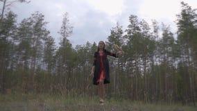 Ένα κορίτσι σε ένα μαύρο και κόκκινο φόρεμα με μια κουκουβάγια στο βραχίονά της περπατά χωρίς παπούτσια μεταξύ ενός κωνοφόρου δασ απόθεμα βίντεο