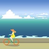 Ένα κορίτσι σε ένα ποδήλατο οδηγά κατά μήκος της ακροθαλασσιάς Διανυσματική απεικόνιση μιας θάλασσας Ελεύθερη απεικόνιση δικαιώματος