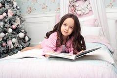 Ένα κορίτσι σε ένα ροζ πλέκει τη ζακέτα στο κρεβάτι με ένα βιβλίο Στοκ φωτογραφίες με δικαίωμα ελεύθερης χρήσης
