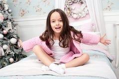 Ένα κορίτσι σε ένα ροζ πλέκει τη ζακέτα στο κρεβάτι Στοκ εικόνα με δικαίωμα ελεύθερης χρήσης