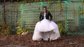 Ένα κορίτσι σε ένα γαμήλιο φόρεμα με μια φοβερή σύνθεση στο πρόσωπό της το φθινόπωρο απόθεμα βίντεο