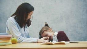 Ένα κορίτσι σε ένα γκρίζο υπόβαθρο κάθεται στον πίνακα τοποθετώντας το κεφάλι της στο πίσω μέρος της καρέκλας Κατά τη διάρκεια αυ απόθεμα βίντεο