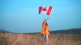Ένα κορίτσι σε ένα κίτρινο σακάκι και τα γυαλιά κρατά στο χέρι της τη σημαία του Καναδά Η σημαία του Καναδά αναπτύσσεται στον αέρ απόθεμα βίντεο