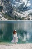 Ένα κορίτσι σε ένα καπέλο και ένα μακρύ φόρεμα περπατά κατά μήκος της λίμνης Lago Di Bries στο βόρειο τμήμα της Ιταλίας στοκ εικόνα
