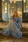 Ένα κορίτσι σε ένα μεσαιωνικό φόρεμα κάθεται στα βήματα Στοκ Φωτογραφία
