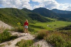 Ένα κορίτσι σε μια κόκκινη κορυφή και τα μπλε σορτς στην άκρη ενός απότομου βράχου στα βουνά Altai, είναι κατωτέρω πράσινοι τομεί στοκ εικόνες με δικαίωμα ελεύθερης χρήσης