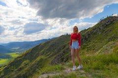Ένα κορίτσι σε μια κόκκινη κορυφή και τα μπλε σορτς στην άκρη ενός απότομου βράχου στα βουνά Altai, είναι κατωτέρω πράσινοι τομεί στοκ φωτογραφίες με δικαίωμα ελεύθερης χρήσης